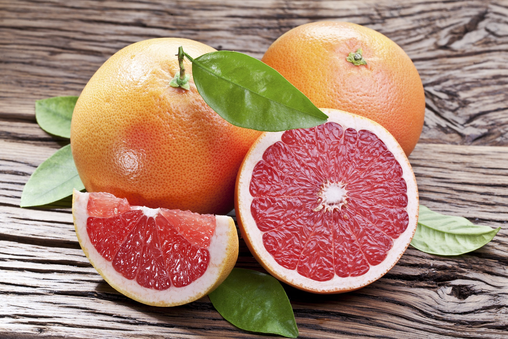 Grapefruits with leaves on a wooden table.